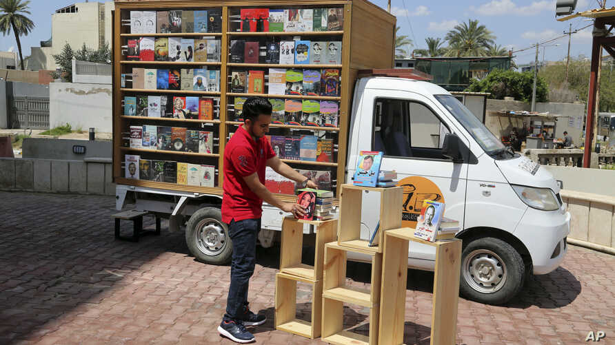 Ali al-Moussawi, the owner of a mobile library truck, arranges his books on a street in Baghdad, Iraq, April 16, 2017.