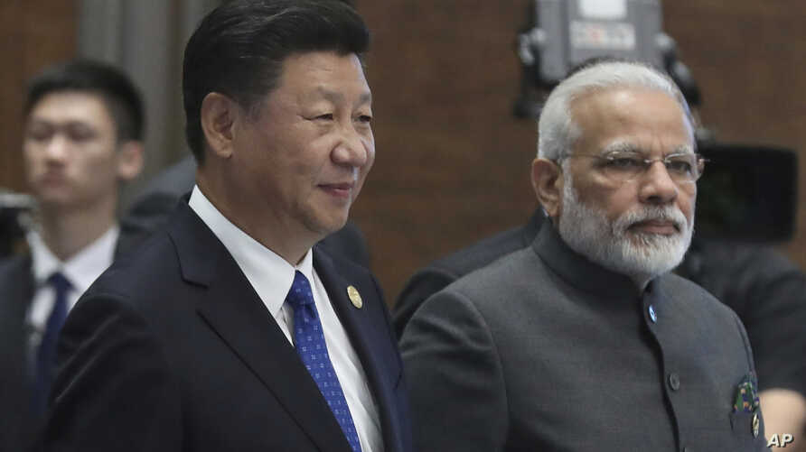FILE - Chinese President Xi Jinping and Indian Prime Minister Narendra Modi arrive for the Dialogue of Emerging Market and Developing Countries on the sideline of the BRICS Summit in Xiamen, China, Sept. 5, 2017.