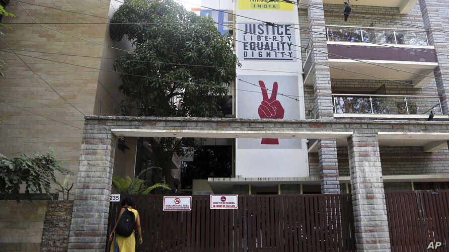 A woman waits to enter the building which houses Amnesty International's office in Bangalore, India, Oct. 26, 2018.