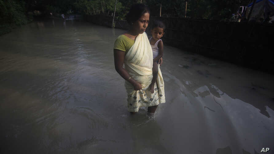 A flood affected woman with her child wades through a flooded road in Chandrapur village, outskirts of Gauhati, Assam state, India, Sept. 25, 2012.