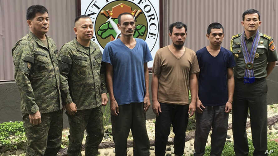 FILE - In this photo released by the Armed Forces of the Philippines, three Indonesian hostages (in civilian clothes) pose with Philippine military officers and an Indonesian military attache in Zamboanga city following their release from captivity i