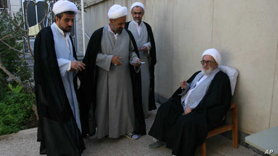 FILE - Grand Ayatollah Hossein Ali Montazeri sits during a gathering  for Eid al-Fitr prayers in Qom,  Oct. 1, 2008. Clerics from left are Mojtaba Lotfi, Abas Ali Fateh, and Montazeri's son Ahmad.