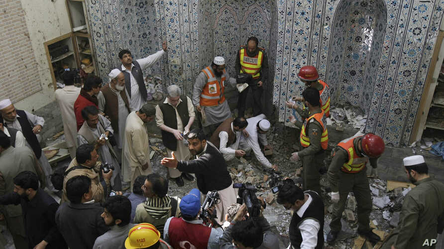 Pakistani security officials and rescue workers examine the site of bomb blast inside a mosque in Peshawar, Pakistan, Mar. 09, 2013.