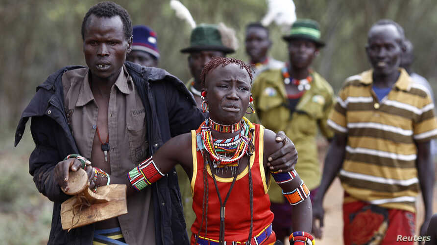 A man holds onto a girl as he brings her back to her family home after she tried to escape when she realized she is to be married, about 80 km (50 miles) from the town of Marigat in Baringo County, Kenya.