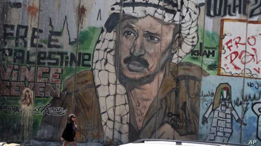 Woman passes near section of Israel's separation barrier depicting Yasser Arafat near the West Bank city of Ramallah, Aug. 8, 2012.