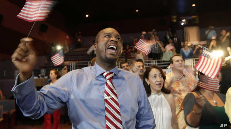 FILE - Jean Naason, 39, of Haiti, left, waves an American flag during a naturalization ceremony administered by the U.S. Citizenship and Immigration Services (USCIS) in Miami, June 5, 2014.