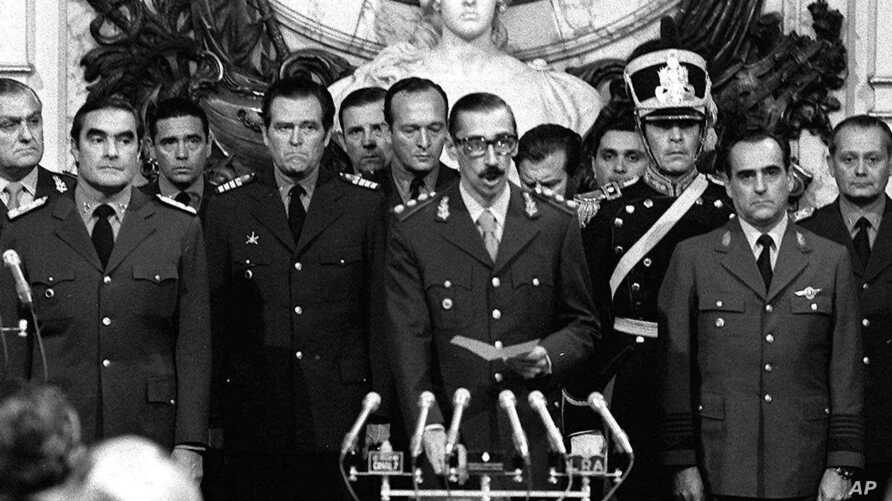 Argentine Dirty War: FILE - In this March 24, 1976 file photo, Gen. Jorge Rafael Videla, center, is sworn-in as president at the Buenos Aires Government House accompanied by Adm. Emilio Massera, second from left, and Brig. Orlando Agosti, second from