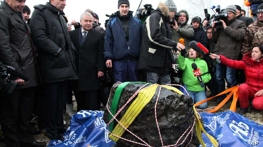 People look at what scientists believe to be a chunk of the Chelyabinsk meteor, recovered from Chebarkul Lake near Chelyabinsk, about 1500 kilometers (930 miles) east of Moscow,  Russia, October 16.