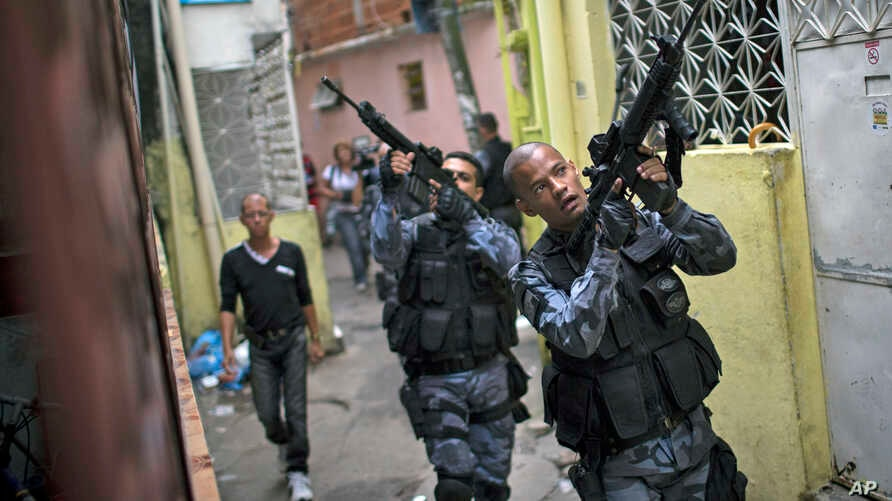 Military police officers patrol in the Roquette Pinto shantytown, part of the Mare slum complex in Rio de Janeiro, Brazil, Wednesday, April 1, 2015. The Brazilian army has begun to pull out of one of Rio de Janeiro's most violent slums, with police a