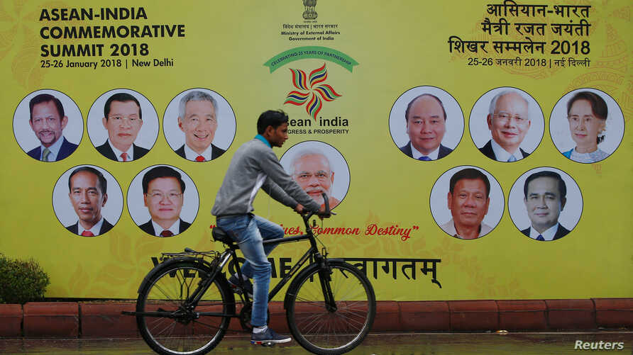 A cyclist rides past an ASEAN-India Commemorative Summit billboard on the side of the road in New Delhi, India, Jan. 23, 2018.