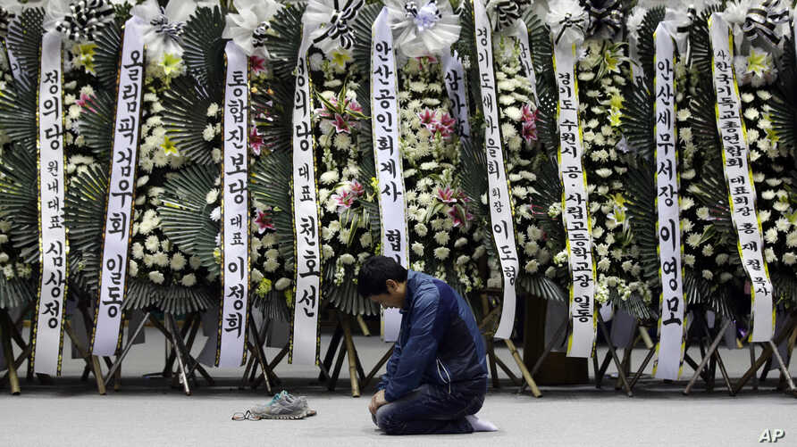 A mourner pays tribute to the victims of the sunken ferry Sewol near condolence flowers at a temporary memorial at the auditorium of the Olympic Memorial Museum in Ansan, South Korea, April 24, 2014.
