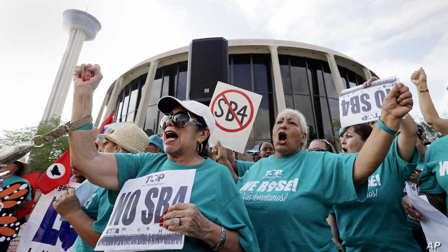 FILE - Lydia Balderas, left, and Merced Leyua, right, join others as they protest against a new sanctuary cities bill outside the federal courthouse in San Antonio, June 26, 2017. A federal judge late Wednesday temporarily blocked most of Texas' toug