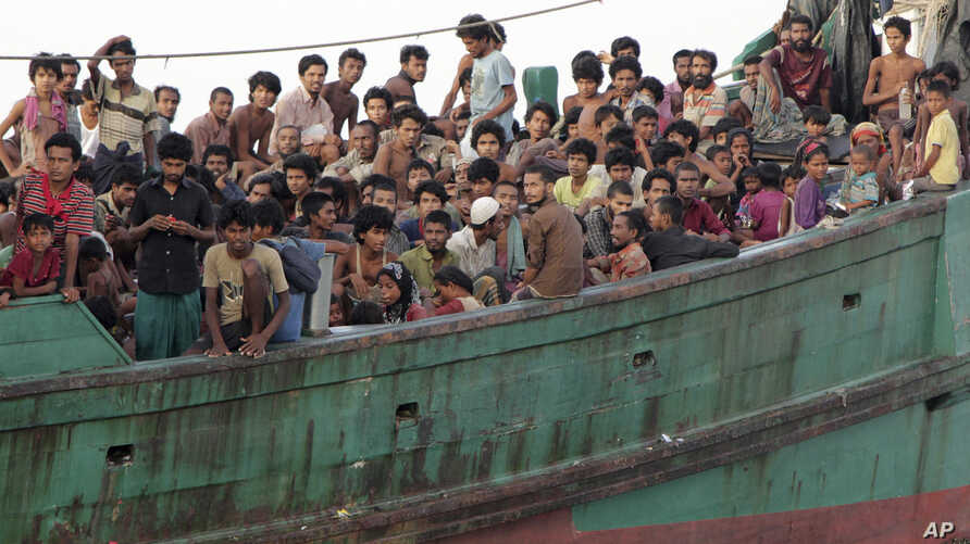 Migrants sit on their boat as they wait to be rescued by Acehnese fishermen on the sea off East Aceh, Indonesia, Wednesday, May 20, 2015. Hundreds of migrants stranded at sea for months were rescued and taken to Indonesia, officials said Wednesday, t...