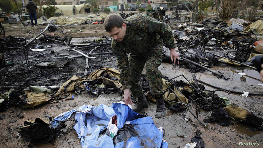 A Russian soldier checks a burned medical tent after rebels launched a mortar shell at a field hospital in west Aleppo, Syria, Dec. 5, 2016.