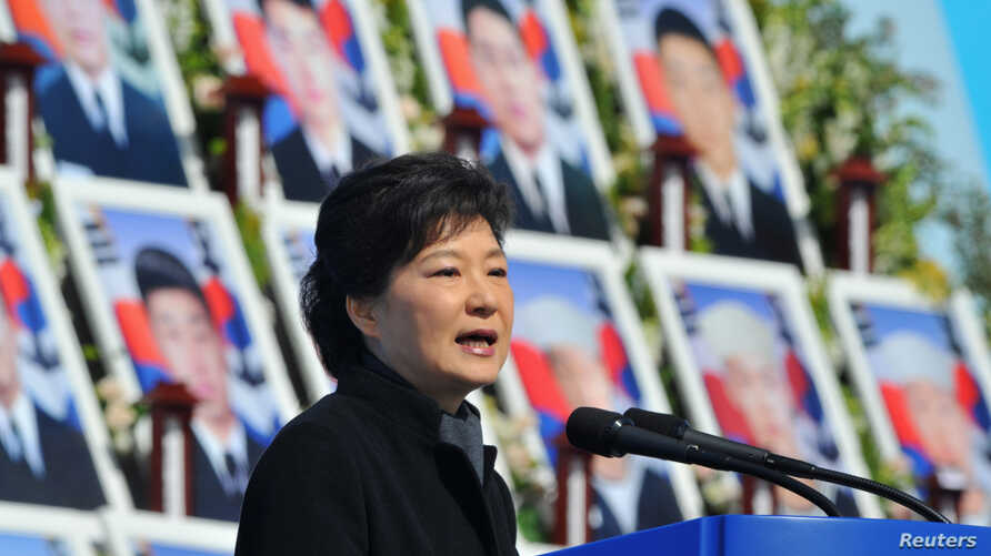 South Korea's President Park Geun-Hye speaks in front of photographs of sailors who died, during an event marking the third anniversary of the sinking of a South Korean naval vessel by what Seoul insists was a North Korean submarine, at the national