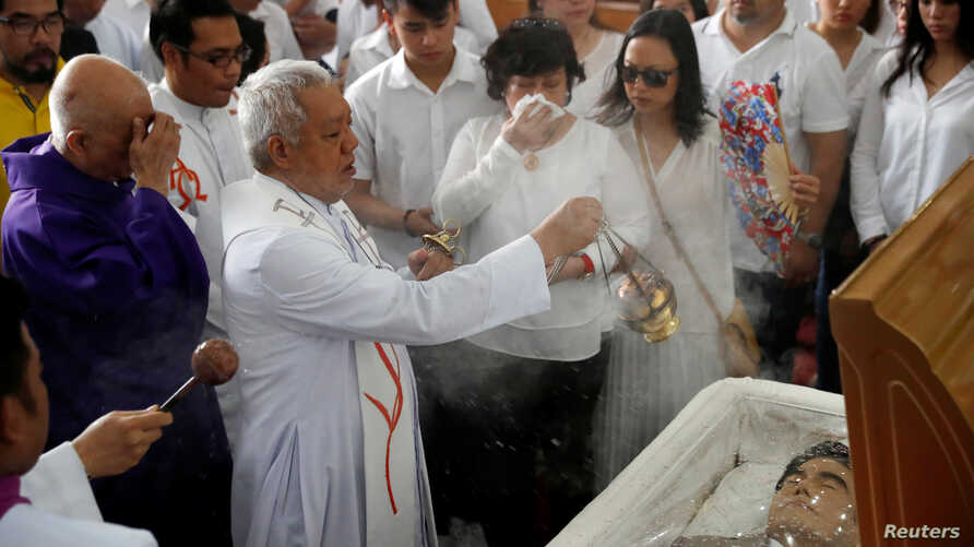 FILE - A priest performs last rites during the funeral mass for Filipino Mayor Antonio Cando Halili, who was assassinated while attending a flag ceremony last Monday, in Tanauan, Batangas, in Philippines, July 8, 2018.