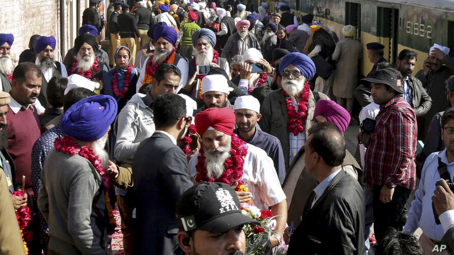 Indian Sikh pilgrims arrive at Wagha railway station to attend the birth anniversary of their spiritual leader Baba Guru Nanak, in Pakistan, Wednesday, Nov. 21, 2018.