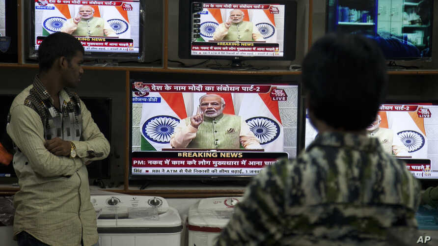 People watch Indian Prime Minister Narendra Modi addressing the nation, on television in Hyderabad, India, Saturday, Dec. 31, 2016.