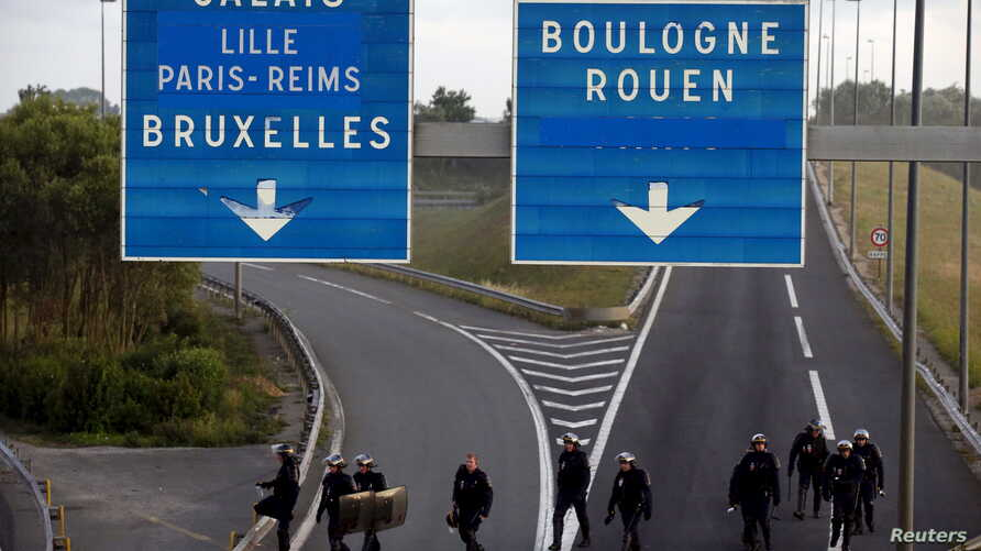 French riot policemen cross the Eurotunnel ramp for trucks after they pushed back migrants who were blocking the road early in the morning, at Coquelles near Calais, France, Aug. 2, 2015.