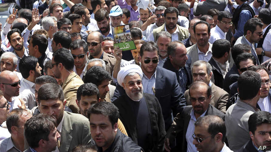 Iranian President Hassan Rouhani, center, joins an annual nationwide pro-Palestinian rally known as Quds (Jerusalem) Day, in Tehran July 25, 2014.