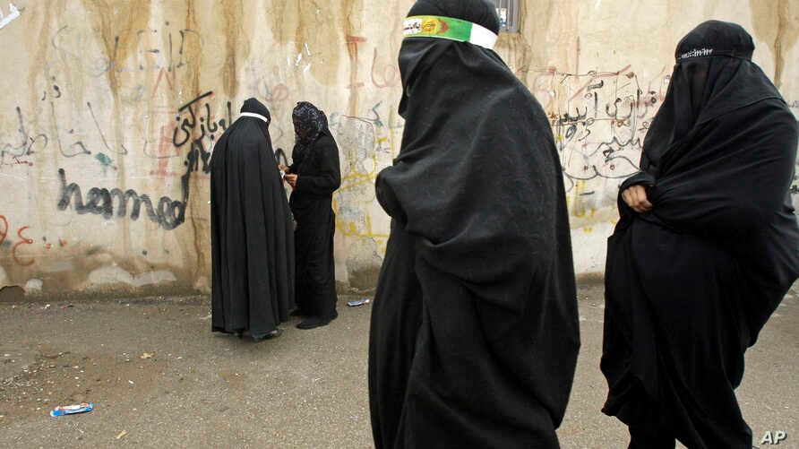 FILE - Veiled Iranian women take part in a mourning ceremony, as they cover their faces symbolically, in the city of Khorramabad, southwest of Tehran.