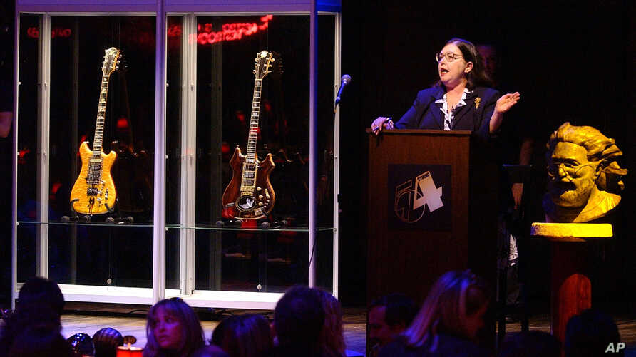 FILE - Guernsey's auctioneer Joanne Grant conducts bidding on guitars previously owned by the late Jerry Garcia during an auction, May, 8, 2002, at Studio 54 in New York.