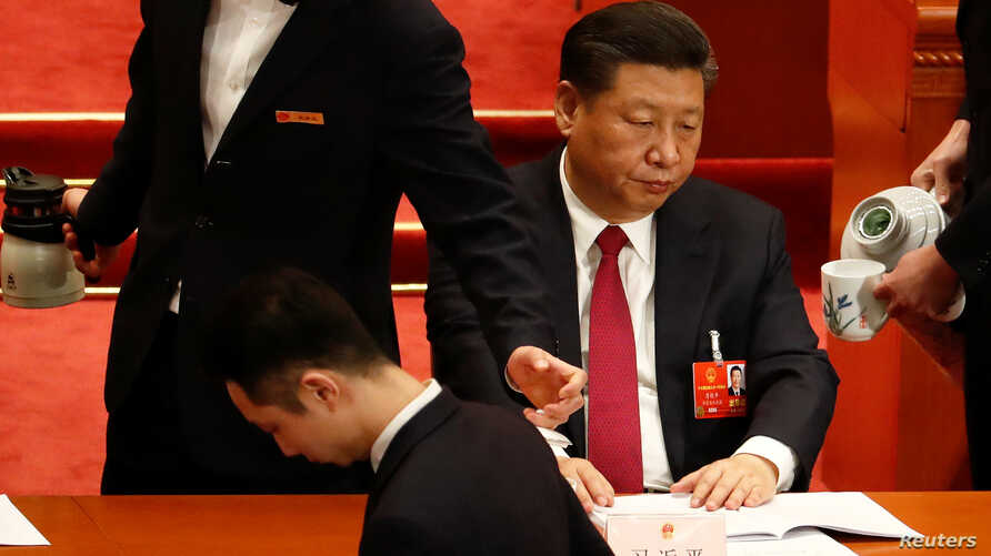 Attendants serve tea for Chinese President Xi Jinping and other officials during the second plenary session of the National People's Congress (NPC) at the Great Hall of the People in Beijing, China March 9, 2018.