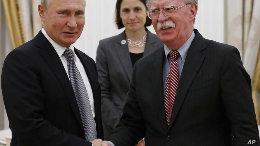 Russian President Vladimir Putin, left, and U.S. national security adviser John Bolton shake hands during their meeting in the Kremlin in Moscow, Oct. 23, 2018.