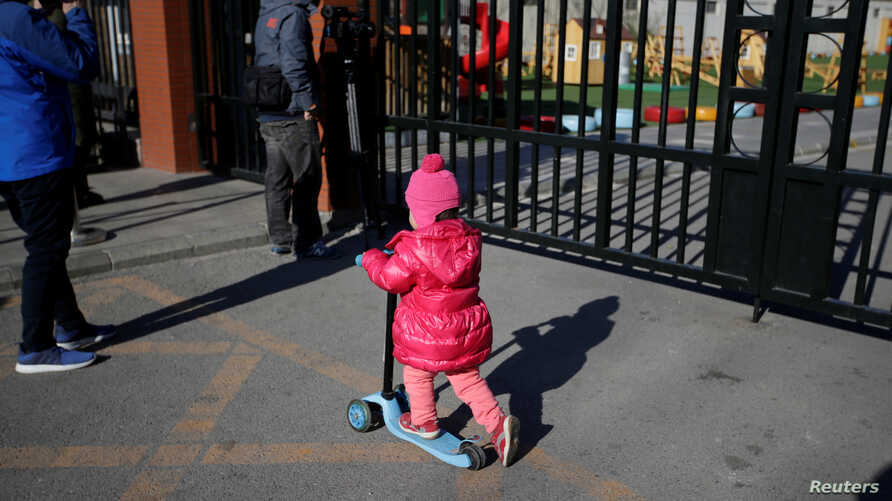 A child plays outside the kindergarten run by preschool operator RYB Education Inc being investigated by China's police, in Beijing, China, Nov. 24, 2017.
