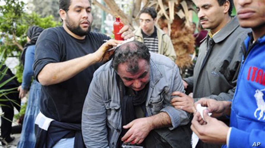 French photojournalist Alfred Yaghobzadeh being treated by anti-government protesters in central Tahrir Square, Cairo, February 2, 2011