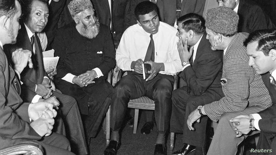 """FILE - Muhammad Ali speaks to Muslims holding a book called """"Towards Understanding Islam"""" written by Sayyid Abul Ala Maududi in London, Britain, May 1966. Ali died late Friday in Phoenix, Arizona, June 3, 2016."""