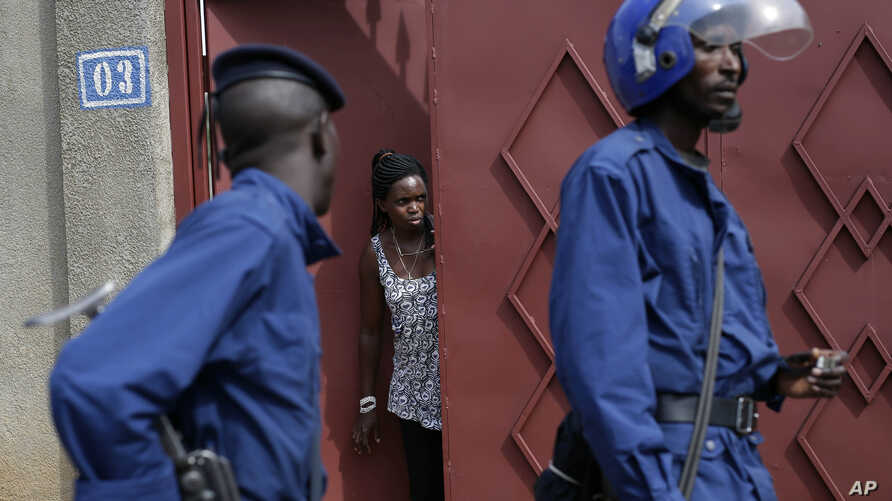 FILE - A resident looks out of house as riot police walk past in the Nyakabiga district, Burundi, May 4, 2015.