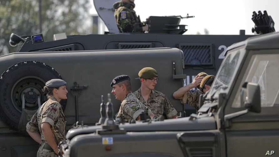 British troops stand near their vehicles after crossing the border from Bulgaria in Giurgiu, Romania, June 1, 2017 to take part in the alliance's Noble Jump 2017 exercise.