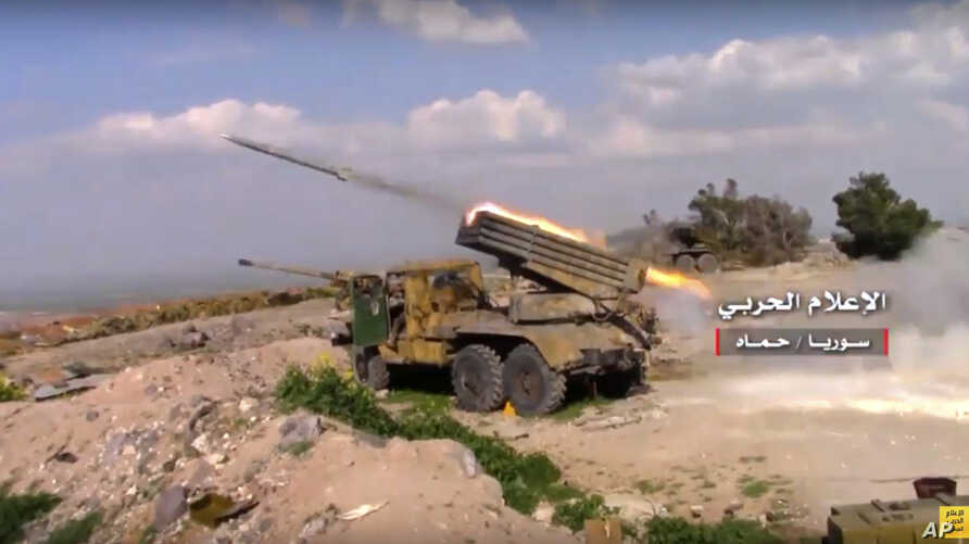 FILE - In this Friday, March 31, 2017 frame grab from video provided by the government-controlled Syrian Central Military Media, Syrian army rocket launcher fires at insurgent groups position, in Hama, north Syria.