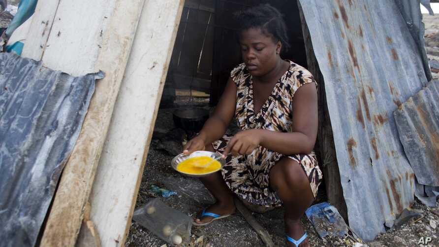 19-year-old Nathanaelle Bernard, who is 7 months pregnant, cooks an omelet in a makeshift hut she is sharing with five members of her extended family, in Coteaux, Haiti, Nov. 1, 2016.