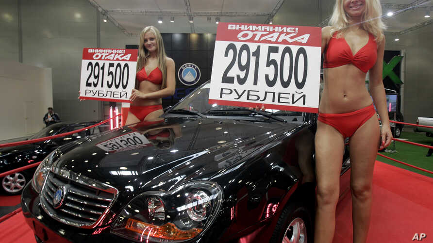 """FILE - Models advertise """"Geely Otaka,"""" a car designed in China, during an auto show in Moscow, Russia."""