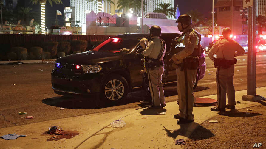 Police stand at the scene of a shooting along the Las Vegas Strip, Oct. 2, 2017, in Las Vegas.