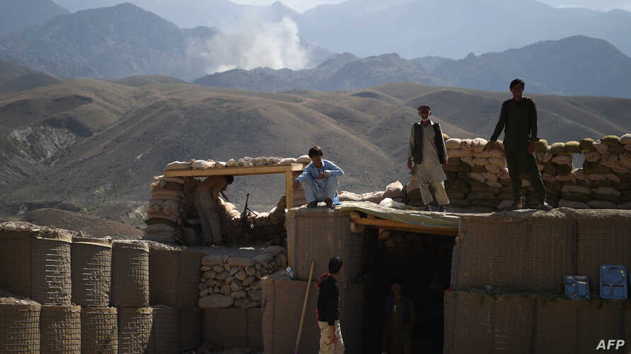 FILE - Afghan Local Police officials look on as smoke rises after an airstrike on Islamic State militant positions in a checkpoint in the eastern province of Nangarhar province, July 7, 2018.