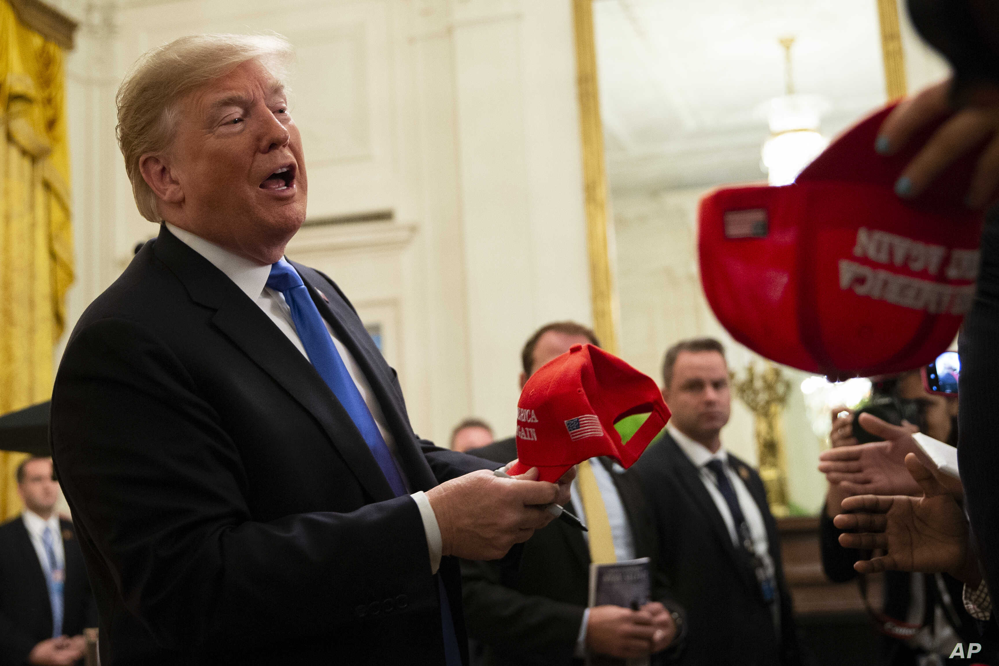 FILE - U.S. President Donald Trump signs Make America Great Again hats at an event at the White House, in Washington, Oct. 26, 2018.