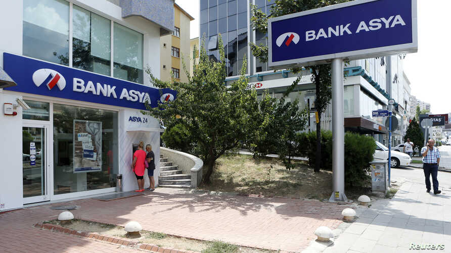 Customers use an ATM machine at a branch of Bank Asya in Ankara, Turkey, Aug. 12, 2014.