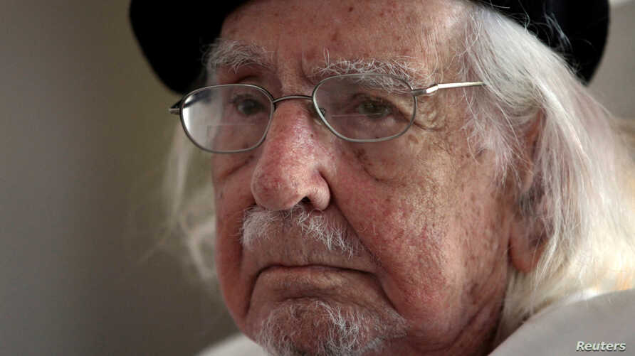 FILE - Nicaraguan poet, priest and Reina Sofia Prize winner, Ernesto Cardenal, who according to local media is being charged for damages against former Tourism Minister Nubia Arcia, listens to his assistant during a meeting at his house in Managua, N
