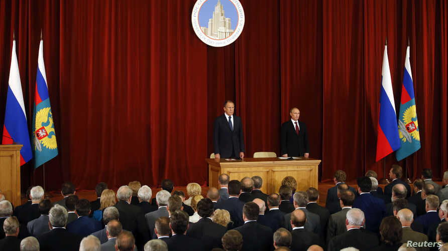 Russian President Vladimir Putin (R, back), Foreign Minister Sergei Lavrov (L, back), Russian ambassadors, envoys and diplomats listen to the national anthem during a meeting in Moscow, July 1, 2014.