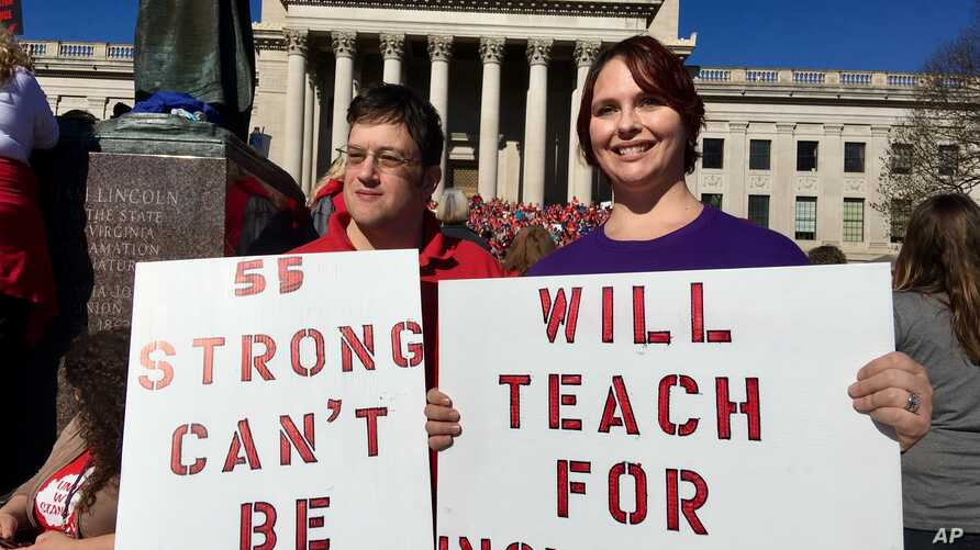Teachers John and Kerry Guerini of Fayetteville, West Virginia, hold signs at a rally at the state Capitol in Charleston, W.Va., Feb. 26, 2018.