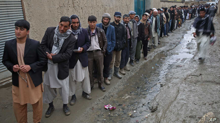 Afghan men line up for registration process before they cast their votes at a polling station in Kabul, Afghanistan, Saturday, April 5, 2014