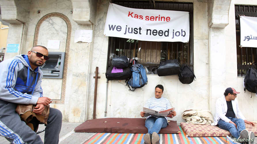 Mohamed Zied el Harizi (C), 37, an unemployed graduate from the city of Kasserine, reads a newspaper as he takes part in a sit-in protest near the Ministry of Vocational Training and Employment demanding the government to provide them with job opport