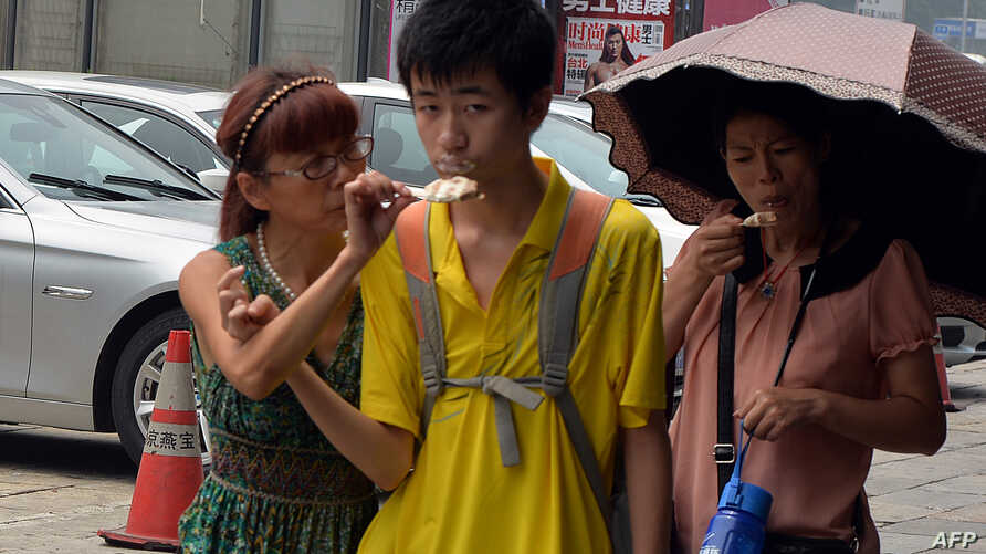 A Chinese family eats ice cream to stay cool as high temperatures continue in Beijing, August 6, 2013.