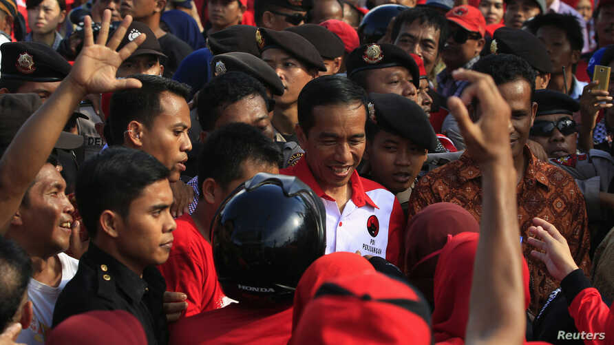 Supporters surround Jakarta governor and presidential candidate Joko Widodo (C) during a PDI-P party campaign in Cilegon, Banten province, March 28, 2014.