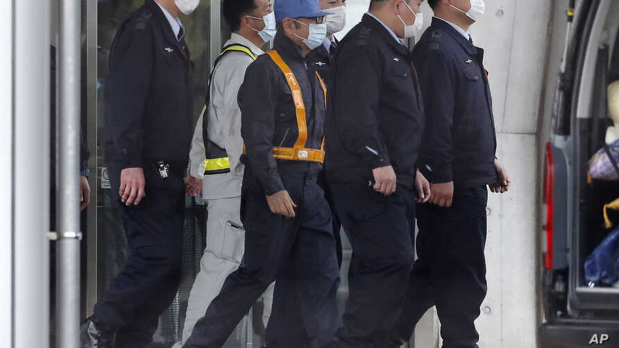 A masked man, center with blue cap, believed to be former Nissan Chairman Carlos Ghosn, walks out with security guards from Tokyo Detention Center in Tokyo Wednesday, March 6, 2019.