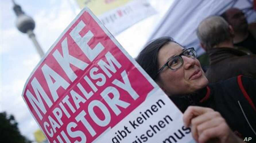 A protester holds a poster during a trade union demonstration against budget cuts, in Berlin, 29 Sept. 2010