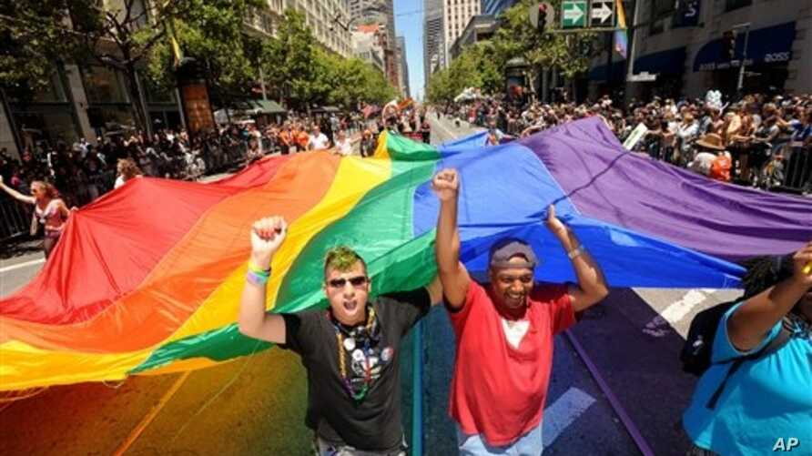 Mark Wilson, right, helps carry a rainbow flag during San Francisco's 42nd annual Gay Pride parade on Sunday, June 24, 2012. (AP Photo/Noah Berger)
